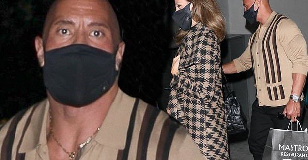 Dwayne 'The Rock' Johnson shows off his muscular physique in a very fitted button-down shirt