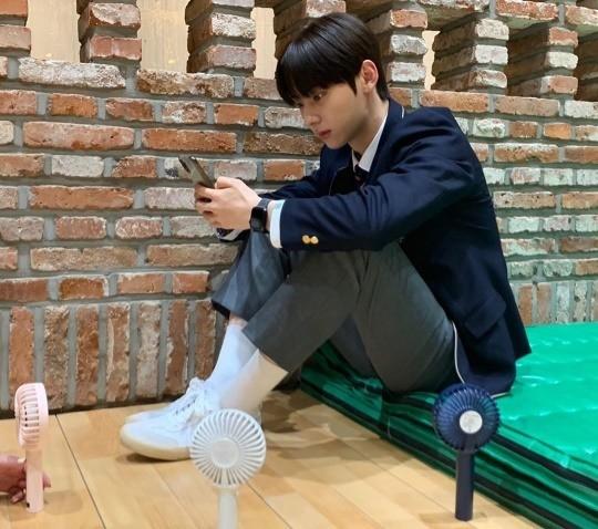 nuest-hwang-minhyun-overcomes-heat-mini-handheld-fans-1